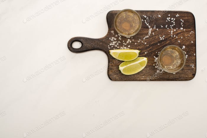 top view of golden tequila with lime, salt on wooden cutting board on white marble surface