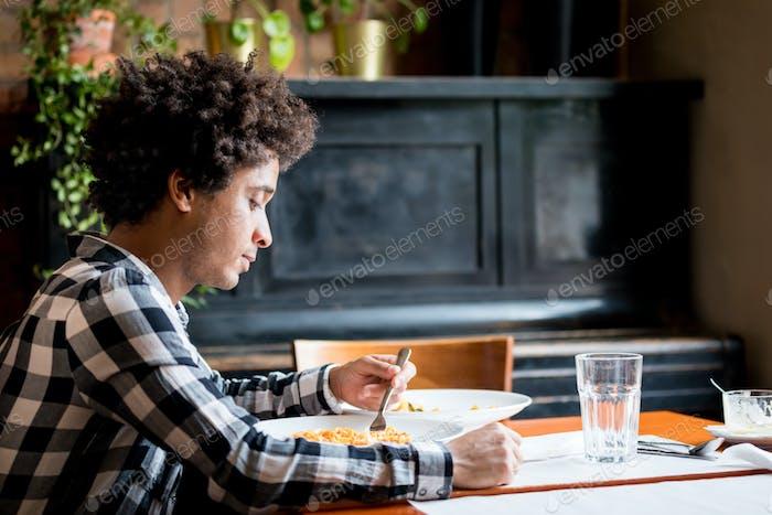 Молодой афроамериканец обедает в ресторане