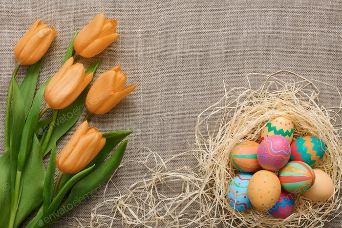 Easter background,eggs, yellow tulips on sackcloth