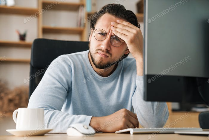 Image of brooding bearded programmer man working with computer