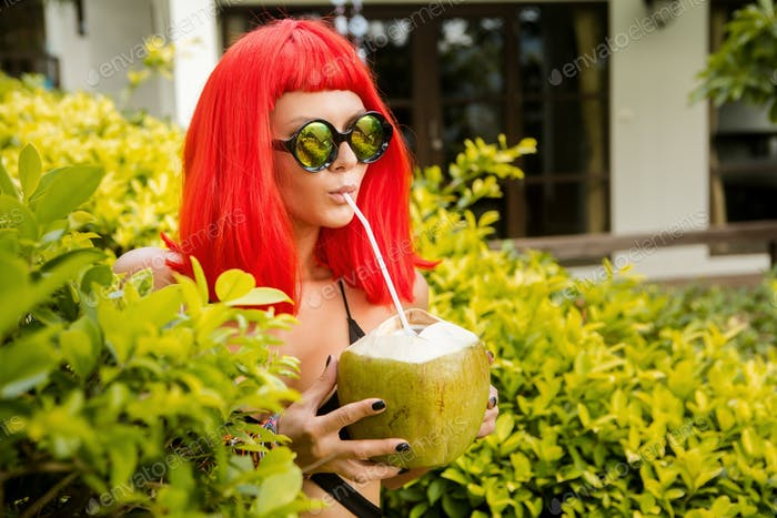 Girl with red hairs drink cold coconut juice.