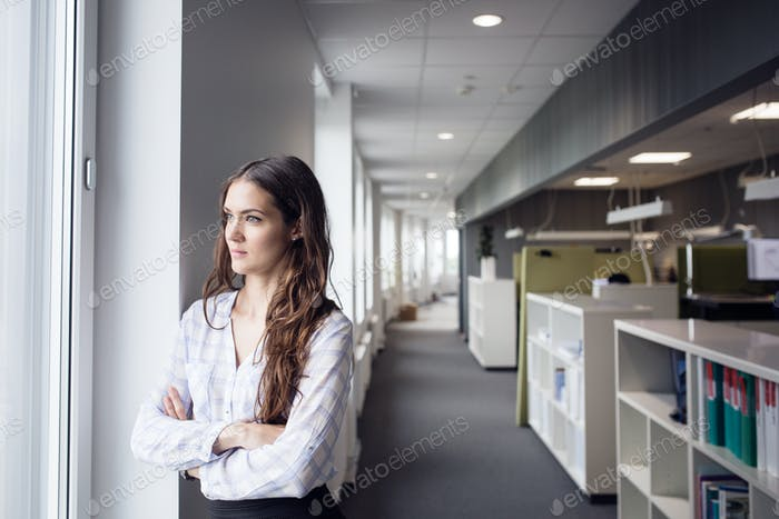 Female architect looking through window