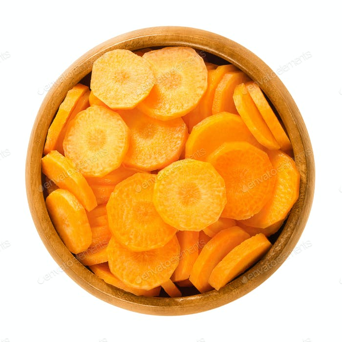 Carrot slices in wooden bowl over white