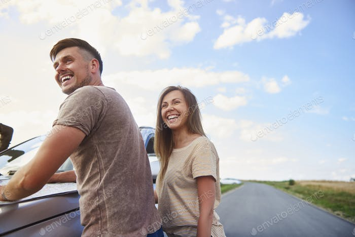 Cheerful couple catching a break during summer road trip