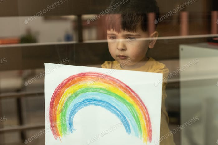 Little kid holding a drawing of a rainbow through the window