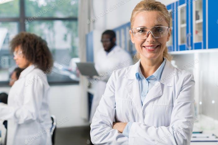 Porträt von lächelnden Frau in weißem Mantel und Schutzbrillen im modernen Labor, Weiblich