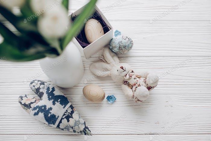 dekorierte und hölzerne Eier und Kaninchen auf rustikalem Holztisch