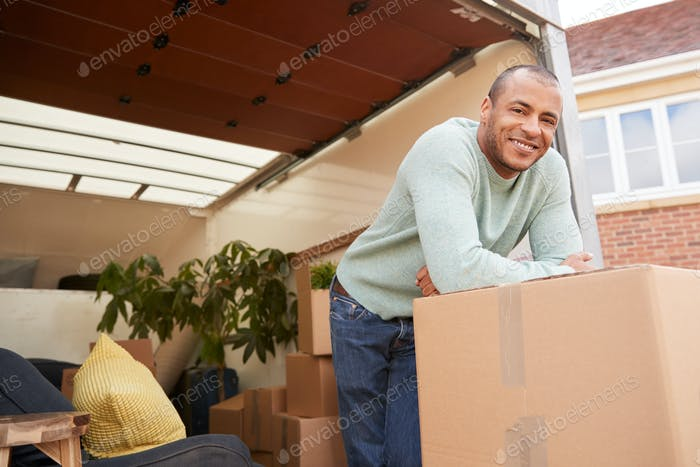 Portrait Of Man Unloading Furniture From Removal Truck Outside New Home On Moving Day