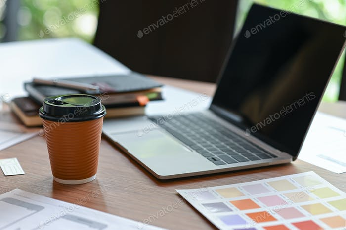 An application designer desk with a mobile screen sketch and take away coffee in the home office.