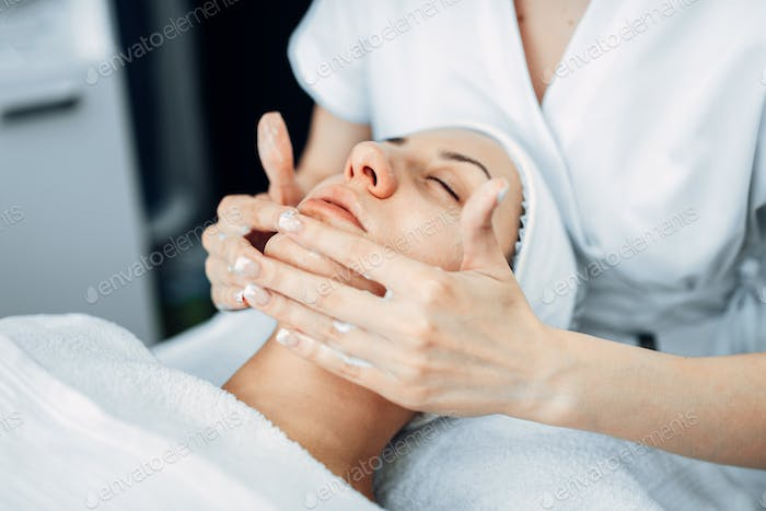 Face massage to female patient, cosmetology clinic