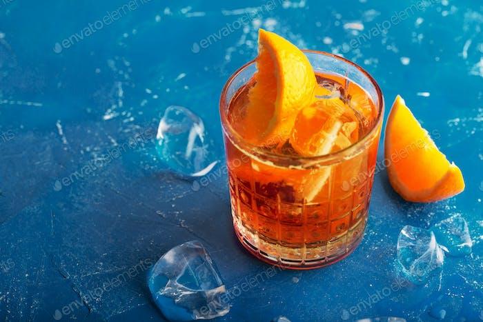 Frischer Eistee Sommercocktail mit Orange und Eis. Hintergrund getönt in modernen blauen Farbe 2020