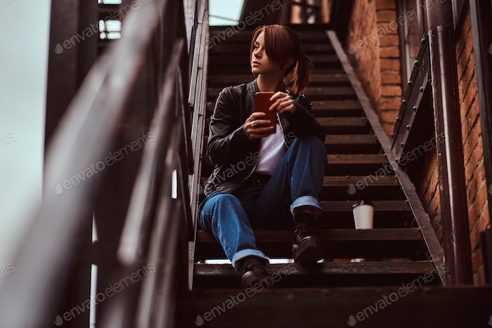 Beautiful hipster girl wearing trendy clothes sitting on stairs outside the cafe