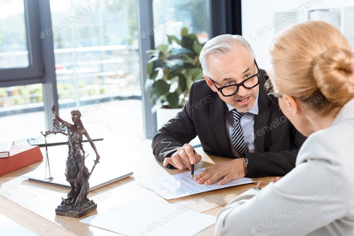 mature serious lawyers discussing business documents in office