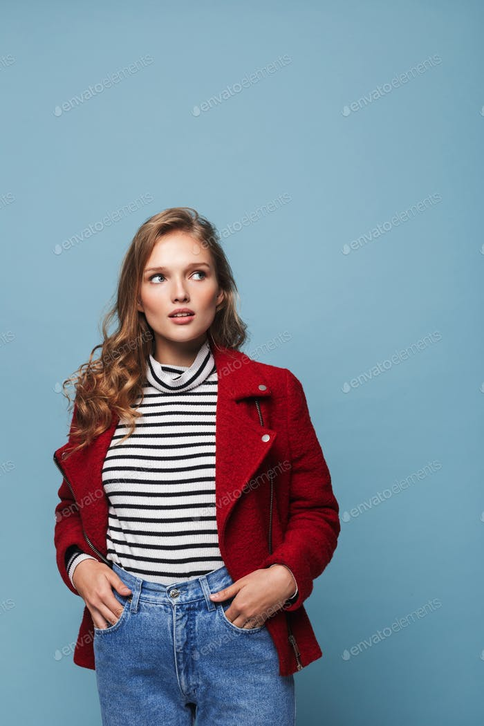 Young beautiful woman with wavy hair in red jacket and jeans dreamily looking aside holding hands
