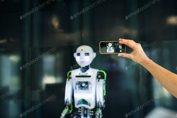 Unrecognizable scientist with smartphone and a robot.