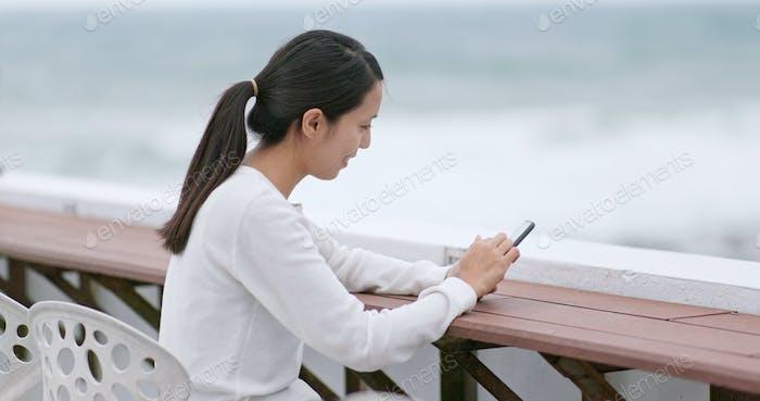 Frau Nutzung des Mobiltelefons im Café am Meer