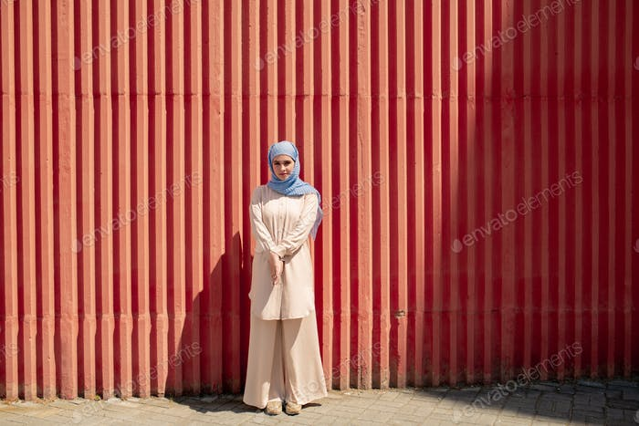 Pretty girl in hijab and casualwear standing by red wall