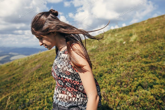 Happy traveler hipster girl walking in sunny mountains