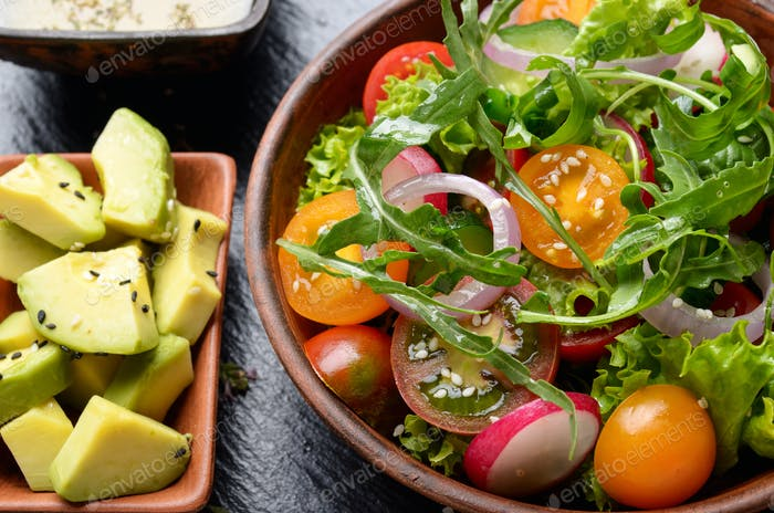 Top view at Clay dish with vegetable salad of lettuce, cherry to