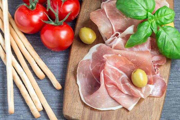 Schinken auf Holzbrett mit grünen Oliven, Tomaten, Grissi