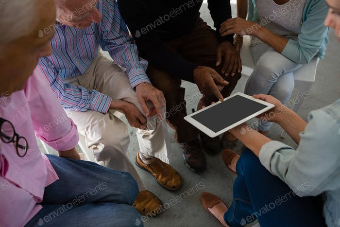High angle view of woman showing tablet to senior adults