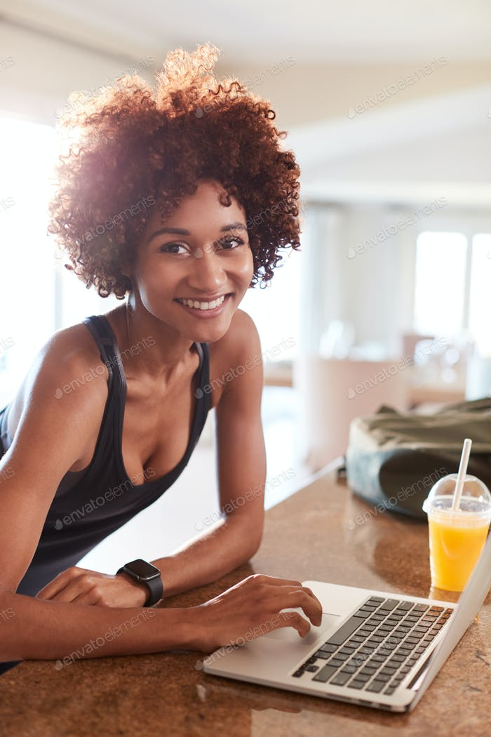 Millennial African American woman checking fitness data on laptop smiling to camera, vertical