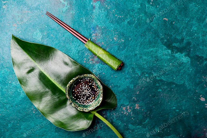 Asian food concept. Chopstick and soysauce soy sauce with white sesame on turquoise background