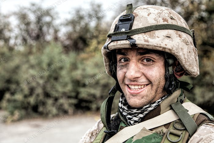 Portrait of smiling army soldier in ragged helmet