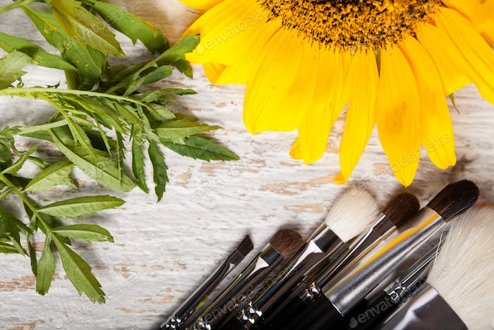 Make up brushes on a table next to wild flowers