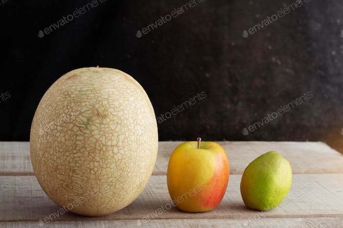Melon and apples on the old wooden