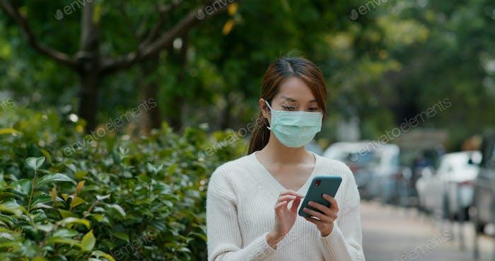 Frau tragen Maske und Verwendung von Mobiltelefon auf der Straße