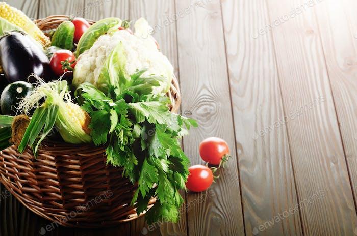 Organic vegetable food ingredients in the basket on wood backgro