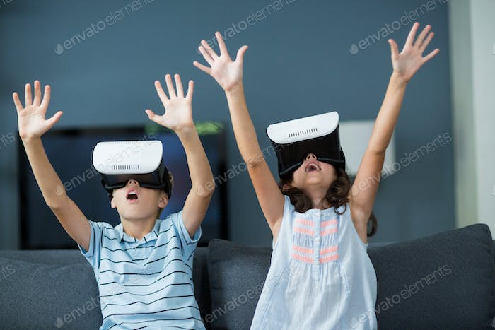 Siblings using virtual reality headset in living room