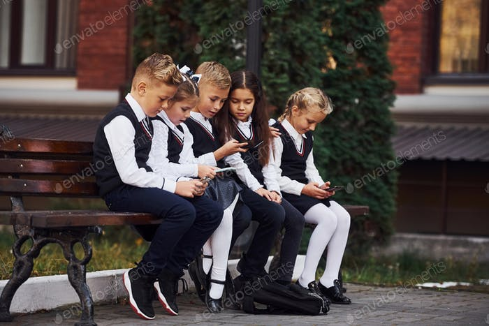 School kids in uniform that sits outdoors on the bench with smartphones