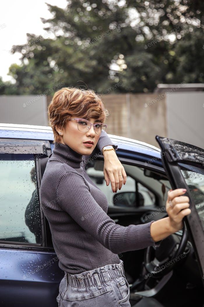 Mujer carrera exitosa posando en coche