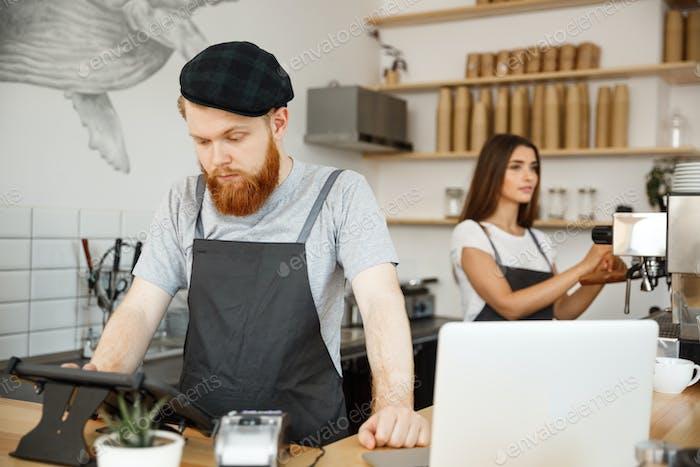 Coffee Business Concept - Junge gutaussehende bärtige Barkeeper, Barista oder Manager, die die Bestellung