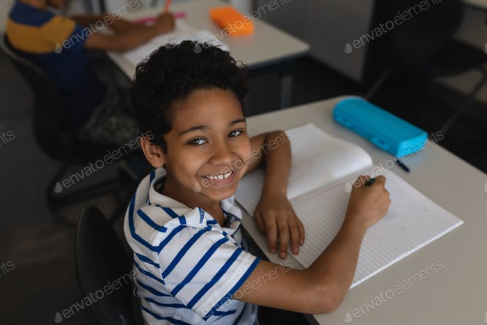 Schoolboy smiling and looking at camera while studying in classroom of elementary school