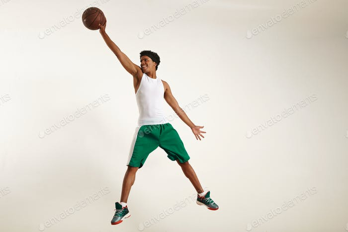 Smiling young black man reaching high for a basketball