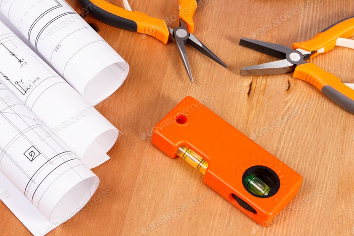 Rolls of electrical drawings or blueprints and orange work tools for use in engineer jobs
