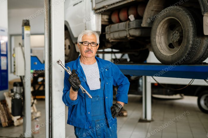 Serious grey-haired man in workwear standing in workshop or hangar