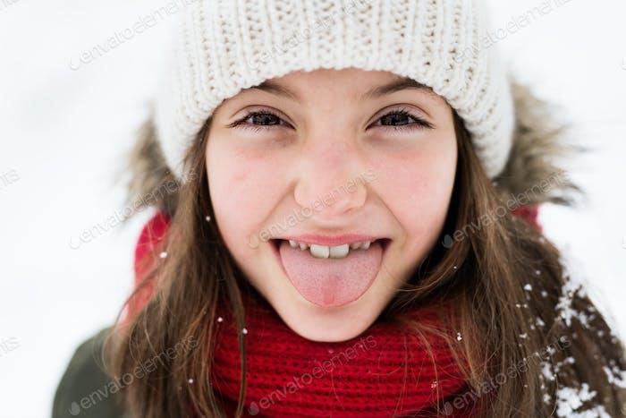 A small girl having fun in snow.