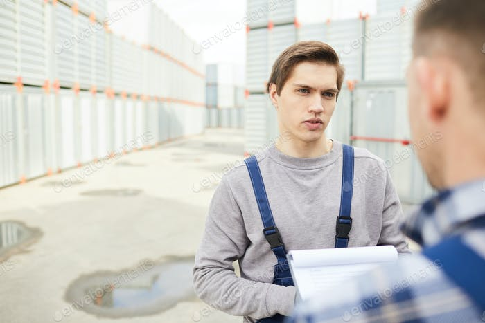 Confused cargo worker talking to colleague