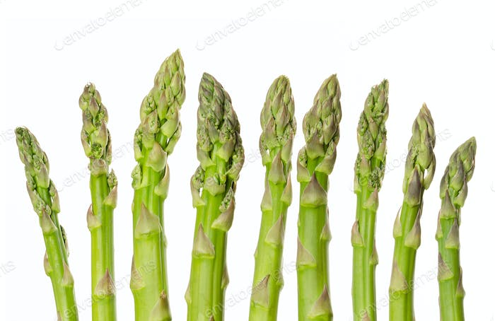 Fresh green asparagus tips in a row over white