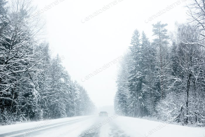 Car driving trough forest highway in snowstorm
