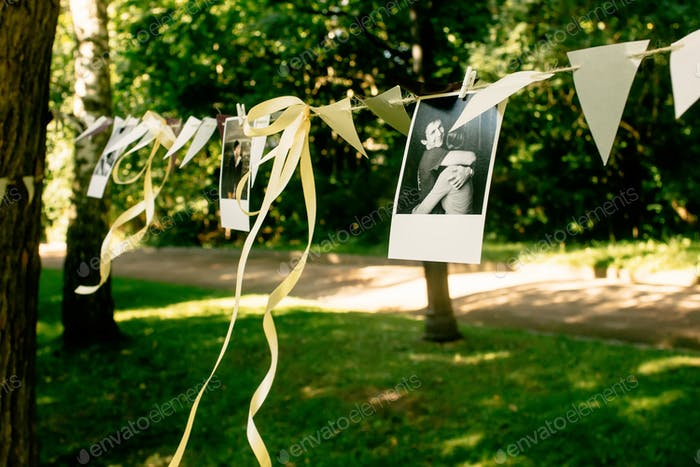 photos of couple and ribbons hanging at celebration place