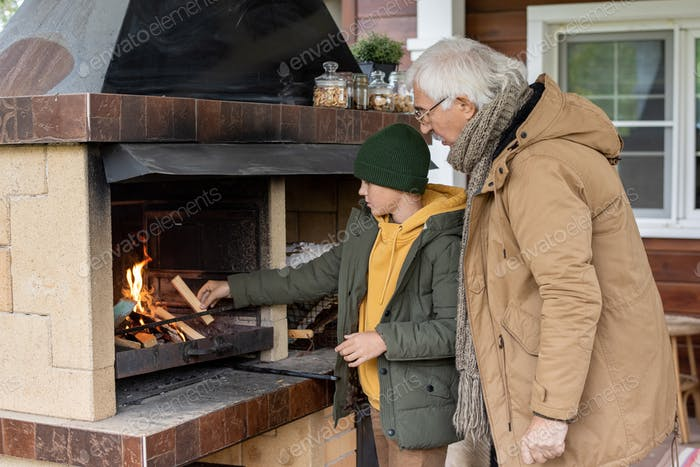 Cute youngster or teenager in warm jacket and beanie standing by fireplace
