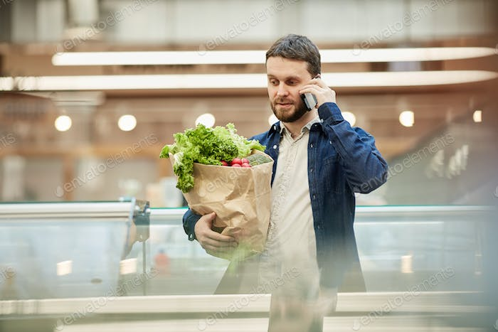 Adult Man Calling by Smartphone in Mall