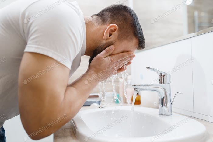 Man washes his face in bathroom, morning hygiene