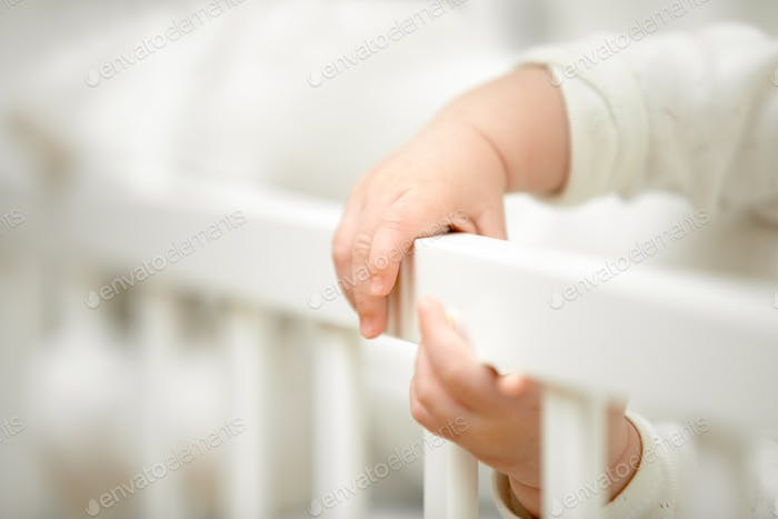 Infant tiny hands in the crib
