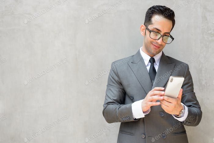 Happy young handsome Persian businessman using phone against concrete wall outdoors